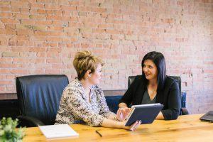 two women in business attire talking