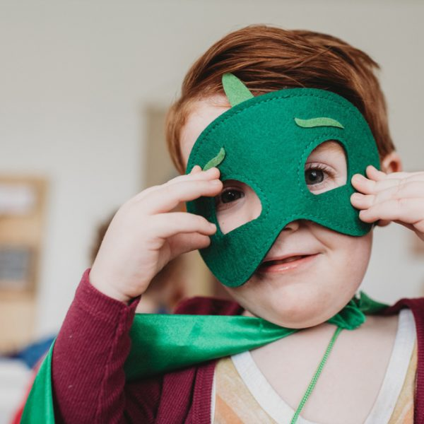 Boy holding a green mask to his face
